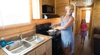 Guests washing dishes in cottage kitchen