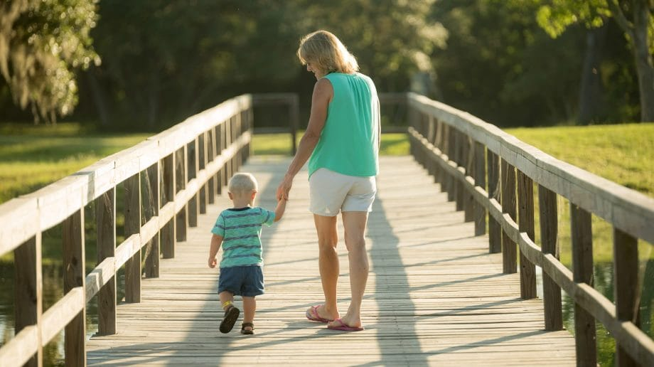 Mother and son walking on bridge