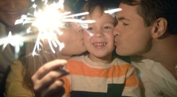 Parents kissing son's cheeks on New Year's Eve