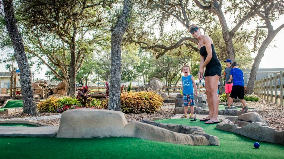 Woman and boy playing putt putt