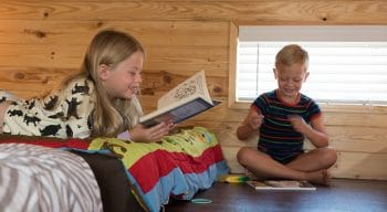 Young kids reading in their cottage