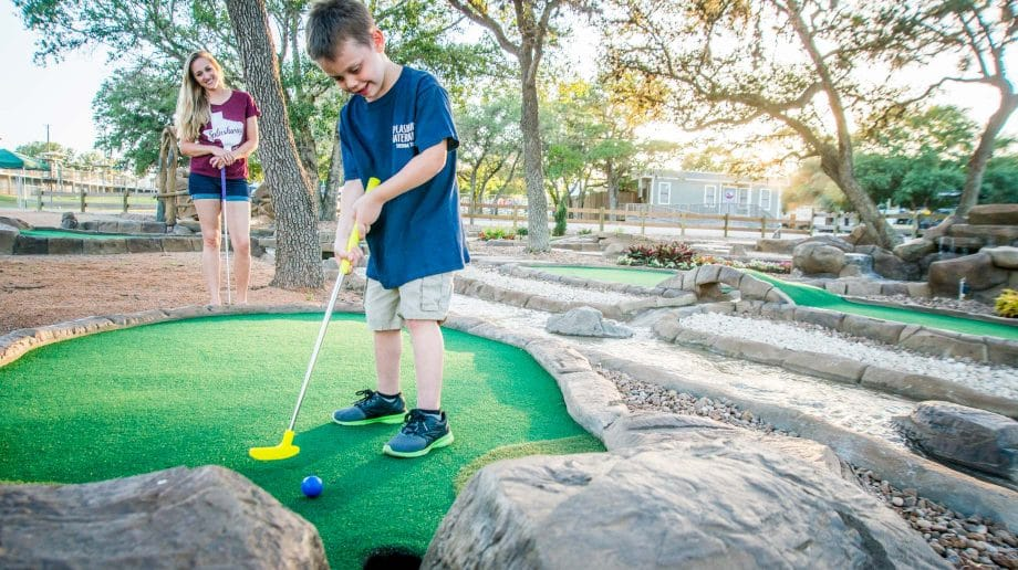 Boy playing putt putt
